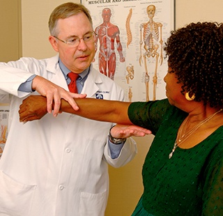 Doctor examining patient's elbow
