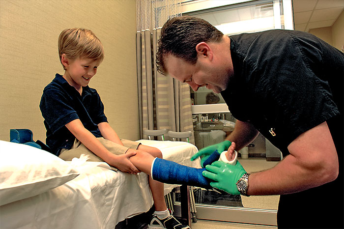 Doctor applying a cast to a patient's leg