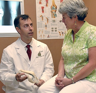 Dr. Joseph E. Broyles, M.D. talking with a patient about joint replacement